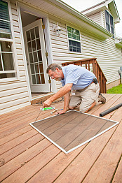 A contractor fixes a screen. Photo by Trigem777/istockphoto.com.