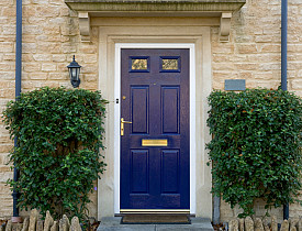 Photo of a blue door flanked by trees via istockphoto.com.