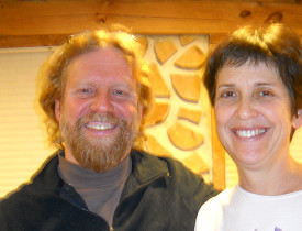 Todd Muller and Patty Smythe in front of a cordwood wall.  Photo: Cris Carl.
