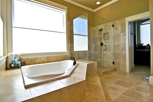 Travertine tile around tub and shower
