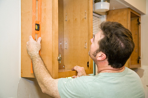 Photo of a carpenter installing kitchen cabinets by lisafx/istockphoto.com.