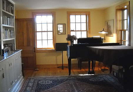 The Brydens split a long, narrow space into a music room and a sitting room. Their grand piano is not at all out of place in their farmhouse.