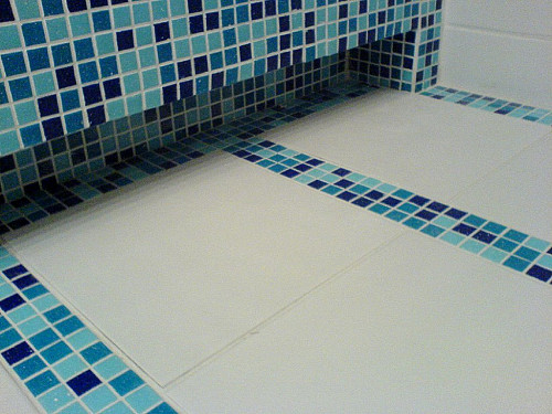 Ceramic bathroom floor with glass tile accent by Jos Zomerplaag/flickr