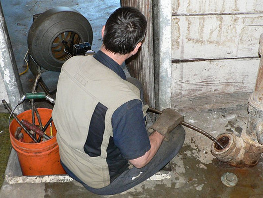 A plumber augers a main sewer line to a house. Photo: Walter Siegmund/Wikimedia Commons.