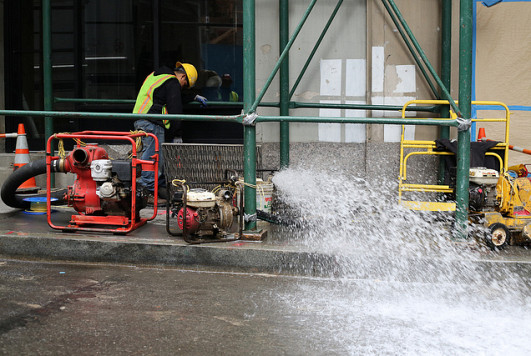 A worker pumps water out of a subway line near Wall St. in lower Manhattan. Photo: WarmSleepy/Flickr