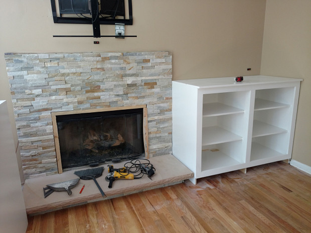 Finished fireplace with damage to hardwood floor
